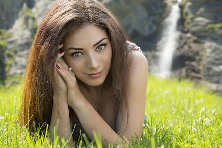 Portrait of gorgeous blue eyed woman laying in grass. Waterfall in background. Stock Photo - 14243461