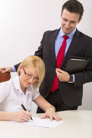 Young beautiful businesswoman signing documents. photo