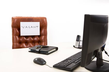 vacant sign: Executive office desk with an employment opportunity sign on leather chair. Isolated on white. Stock Photo