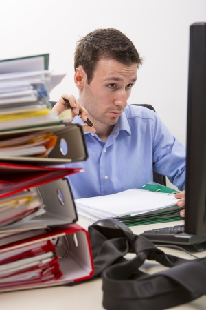 Confused accountant looking at some info on the display of his computer, surrounded by huge piles of documents. Stock Photo