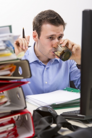 Confident accountant doing financial reports in front of his computer, drinking water, surrounded by huge piles of documents. Stock Photo