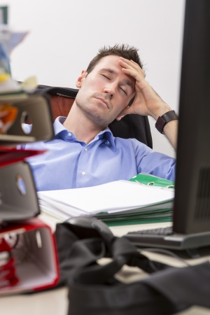 Exhausted office worker falls asleep in front of his computer, surrounded by a pile of file folders photo
