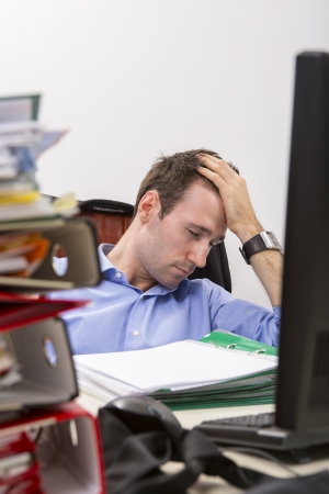 Ofiice worker falls asleep by exhaustion at a desk full of massive stack of file folders.