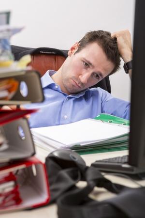 オフィス実業団彼の机の文書の完全に圧倒される式を示します。