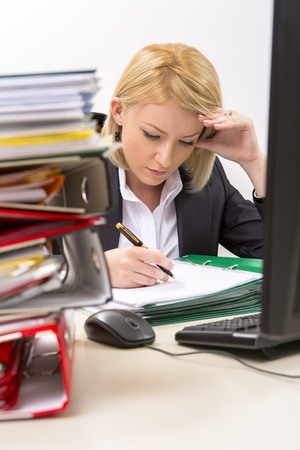 Confident blonde businesswoman filing documents in front of his computer, supporting his head with her left hand, surrounded by huge piles of documents. photo