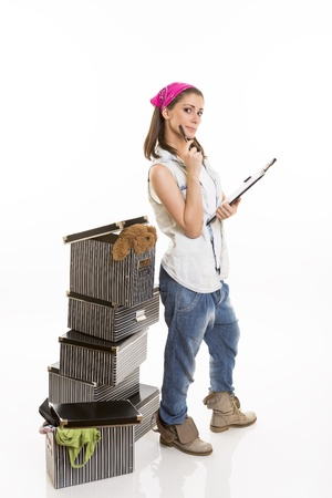 Casual dressed woman keeping track of packed stuff on her board, standing near a stack of striped boxes, looking at the camera. Stock Photo