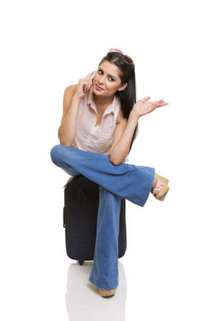Pretty businesswoman sitting cross-legged on suitcase, talking to the cellphone and doing hand gesture. photo