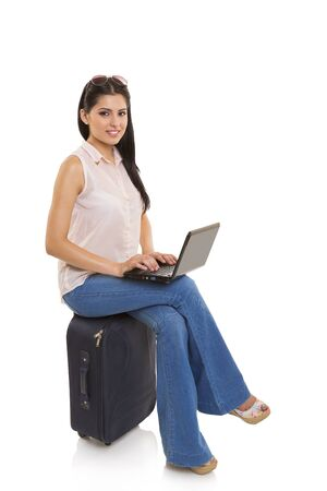 Attractive businesswoman sitting on suitcase and typing on her black laptop on white background.