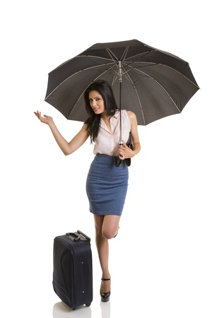 Traveling pretty business woman holding opened black umbrella and checking for rain. Isolated on white.