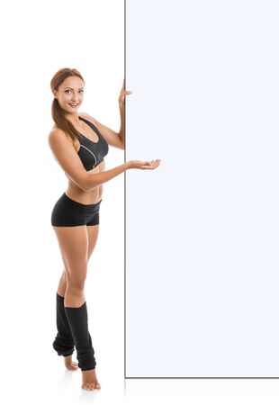 Beautiful fitness woman holding large white blank sign banner. Isolated on white. photo
