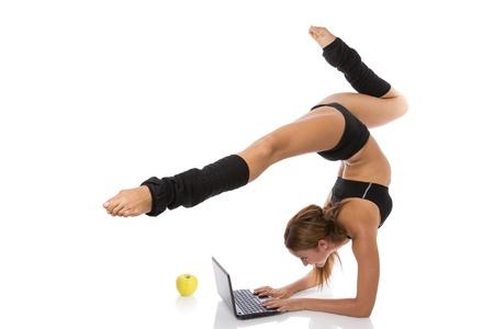 Mujer atlética que se coloca en una postura flexible y escribiendo en el teclado de la computadora portátil, aislado en blanco