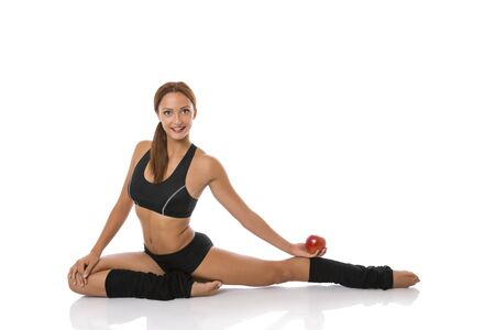 Beautiful fitness woman doing stretching exercise and holding red apple in one hand, Isolated on white  photo