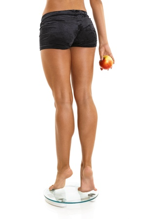 Woman perfect shaped legs on scale with red apple in hand.Isolated on white. photo