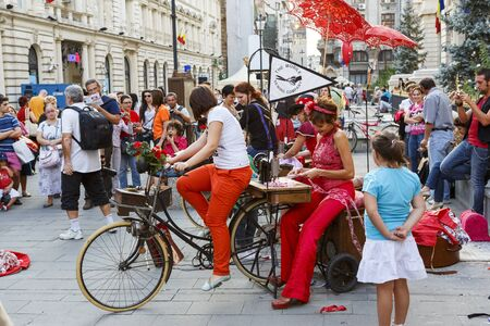 bucharest: BUCHAREST, ROMANIA - SEPTEMBER 13: The Mobile Sewing Company artists sew at pedal-powered sewing machine during B-FIT in the Street Festival on September 13, 2012 in Bucharest, Romania.