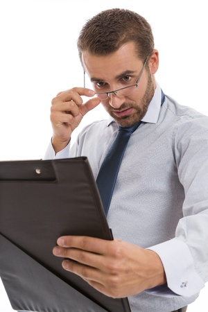 Young concerned accountant looking over eyeglasses at black folder with documents, over white background. Stock Photo