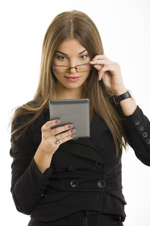 Beautiful surprised long-haired young woman looking over her eyeglasses at her e-book reader display over white background. photo