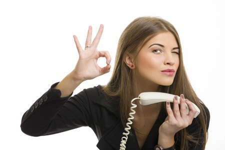 Portrait of attractive young business woman gesturing okay sign after successful deal on phone over white background. photo
