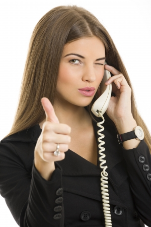 Portrait of attractive young business woman gesturing okay sign while talking on phone over white background. Stock Photo - 16010670