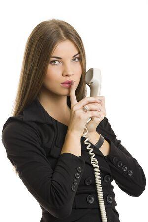 discreto: Retrato de mujer de negocios atractivo joven que gesticula mantener signo silencio mientras habla por teléfono sobre fondo blanco.