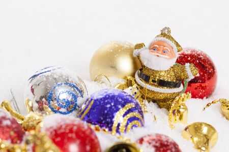 Joyful Santa Claus figurine surrounded by colorful Christmas balls in snow Stock Photo - 16183730