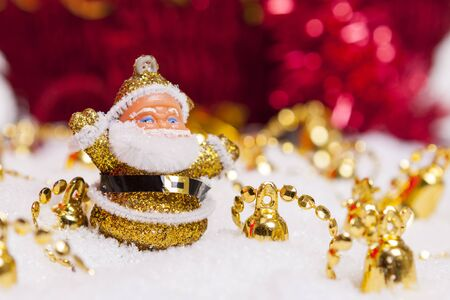 Happy Santa Claus figurine surrounded by Christmas golden bells and snow  Stock Photo - 16183734