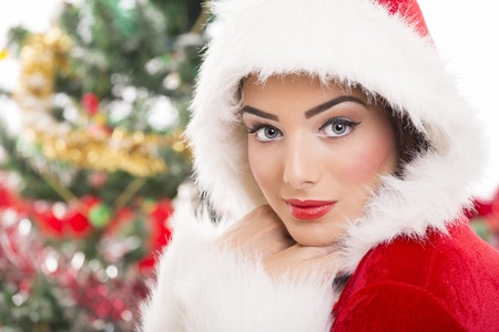 Portrait of charming Santa girl over blurred Christmas background.