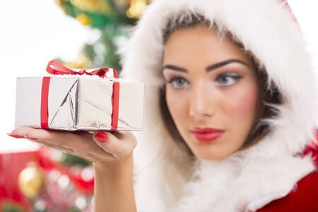 Beautiful Santa girl looking at silver Christmas gift box in her hand. Selective focus on gift box. Stock Photo - 16409277