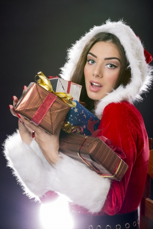 Surprised Santa girl holding many Christmas gift boxes over dark background. Stock Photo - 16409287