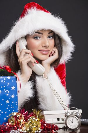 Portrait of smiling Santa girl speaking on the phone with alarm clock, gift box and decorations on desk. photo