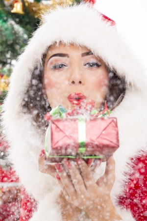 Beautiful Santa girl blowing snow off the silver Christmas gift box in her hand. photo