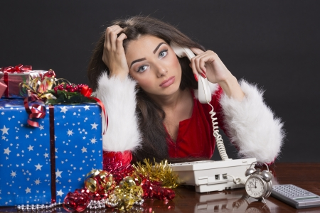 Stressed beautiful Santa girl sitting at desk and speaking on phone surrounded by Christmas presents, decorations, alarm clock and calculator over dark background. Stock Photo - 16409285