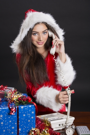 Beautiful smiling Santa girl answering Christmas calls over dark background. photo