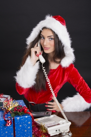 Beautiful Santa girl answering the phone over dark background. photo