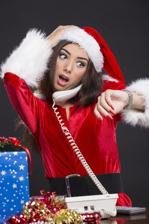 Desperate Santa girl speaking on the phone and checking the time on her wristwatch over dark background. photo