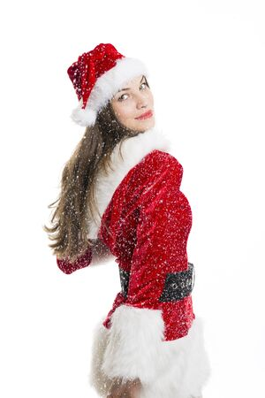 Beautiful happy woman dressed with Santa costume and snow falling on her over white background. Stock Photo