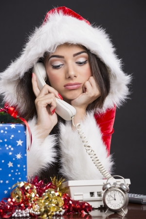 Portrait of unhappy Santa girl speaking on the phone with alarm clock, gift box and decorations on desk. Stock Photo - 16716252