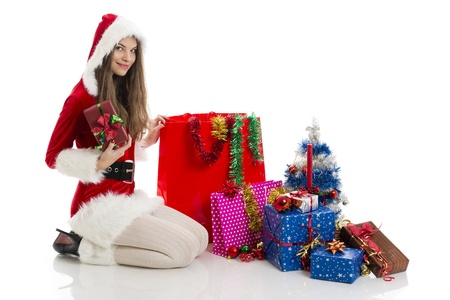 Beautiful Christmas sexy girl wearing Santa Claus clothes holding red gift box, near big shopping bags and presents, over white background. Stock Photo