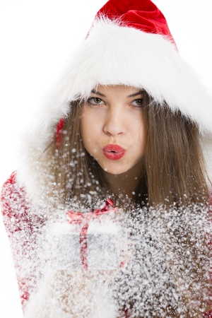 Portrait of beautiful Santa girl blowing snow off the silver Christmas gift box in her hand  photo