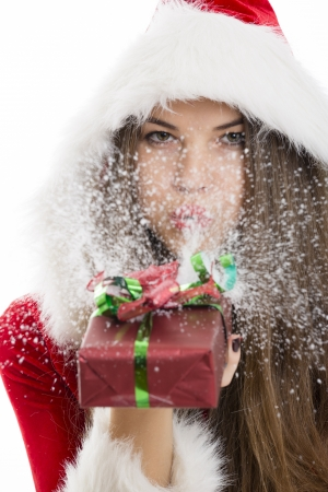 Beautiful Santa girl blowing snow off the red Christmas gift box in her hand Stock Photo - 16791154
