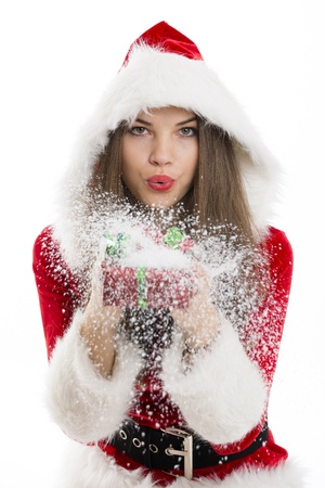 Beautiful Santa girl blowing snow off the Christmas gift box in her hand  photo