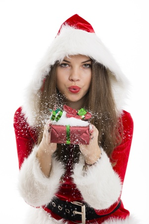 Beautiful Santa girl blowing snow off the red Christmas gift box in her hand  photo
