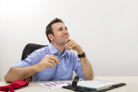 Young executive holding his chin on his hand and lost in happy thoughts at work  Stock Photo