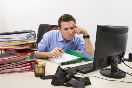 ドキュメントの巨大な山に囲まれて、彼のコンピューターのディスプレイ上のいくつかの情報を見て混乱している会計士