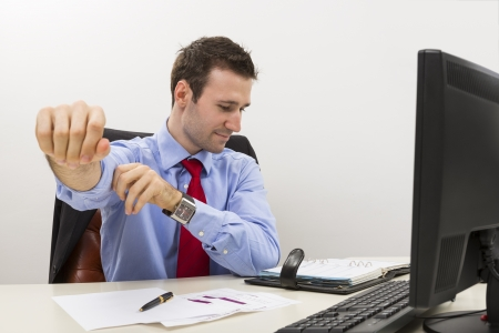 Handsome young employee at office rolling up the shirt sleeve as a positive ready to work gesture  Stock Photo