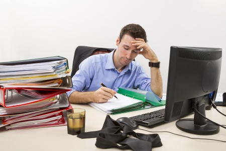 Confident businessman doing paperwork in front of his computer surrounded by huge piles of documents