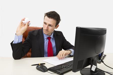 オフィスで彼のコンピューターの前に紙を丸めてを投げて失望のマネージャー 写真素材