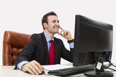 ハンサムな実業家彼のコンピューターの使用中のオフィスで積極的に笑顔 写真素材