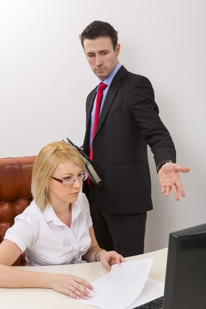Unhappy business man debating with blond woman business  partner about some data on computer display. photo