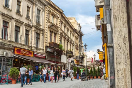 BUCHAREST, ROMANIA - JUNE 1: Group of tourists stroll down a crowded cobblestone street of the old historical center Lipscani on June 1, 2012 in Bucharest, Romania.