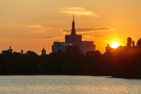 universally: Sunset over House of the Free Press (still universally known as Casa Scanteii). View from the lake in Herastrau Park, Bucharest, Romania.